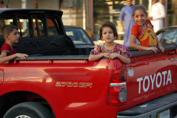 Retrieved photo.  Kids in bed of truck.