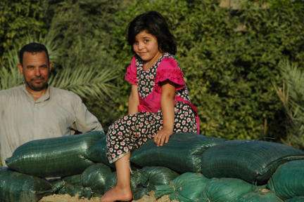 Little girl on sandbags at the home of brothers who fought against ISIS