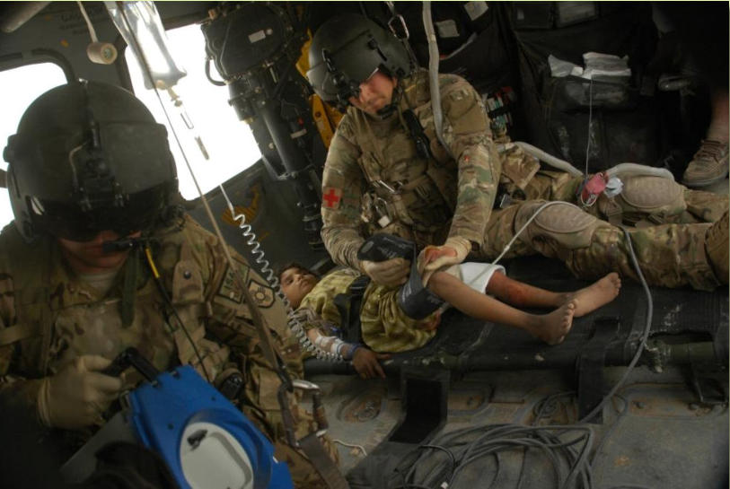Spc. Armando Martinez, crew chief, of the New Mexico National Guard (L) and Sgt. Eric Papp, medic, of the Minnesota National Guard,(R) are seen tending to an injured Afghan little girl.  March 3, 2012