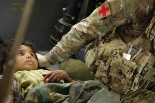 Little Afghan on medevac helicopter looking up at US Medic during flight.