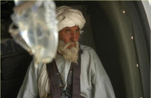 Father of injued little Afghan girl seen here looking out window of US Blackhawk medevac helicopter.