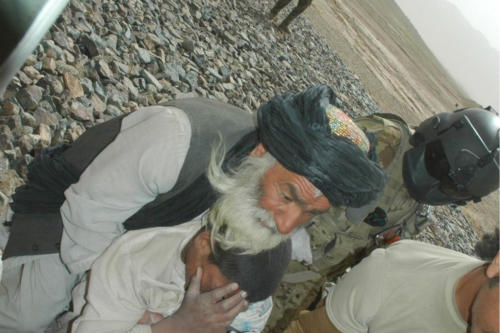 Afghan father seen here loading his son onto medevac helicopter.  His son was injured in the eyes from an IED blast.