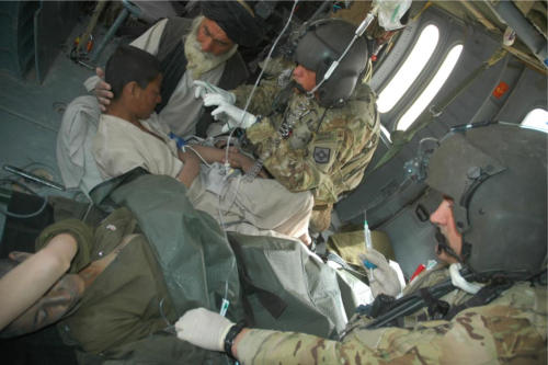 Sgt Heath Perry, front, and SSGT Jason Bowen, rear, seen here assisting two injured boys from an IED blast as medevac helicopter takes them to medical facility.