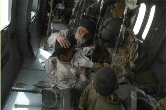 SSGT Jason Bowen, crew chief on medevac helicopter, is seen here assisting injured child.
