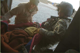 Sgt Menzie (R) and Sgt Hayes (L) carry the injured ANA by blanket to STP upon arrival of medevac helicopter